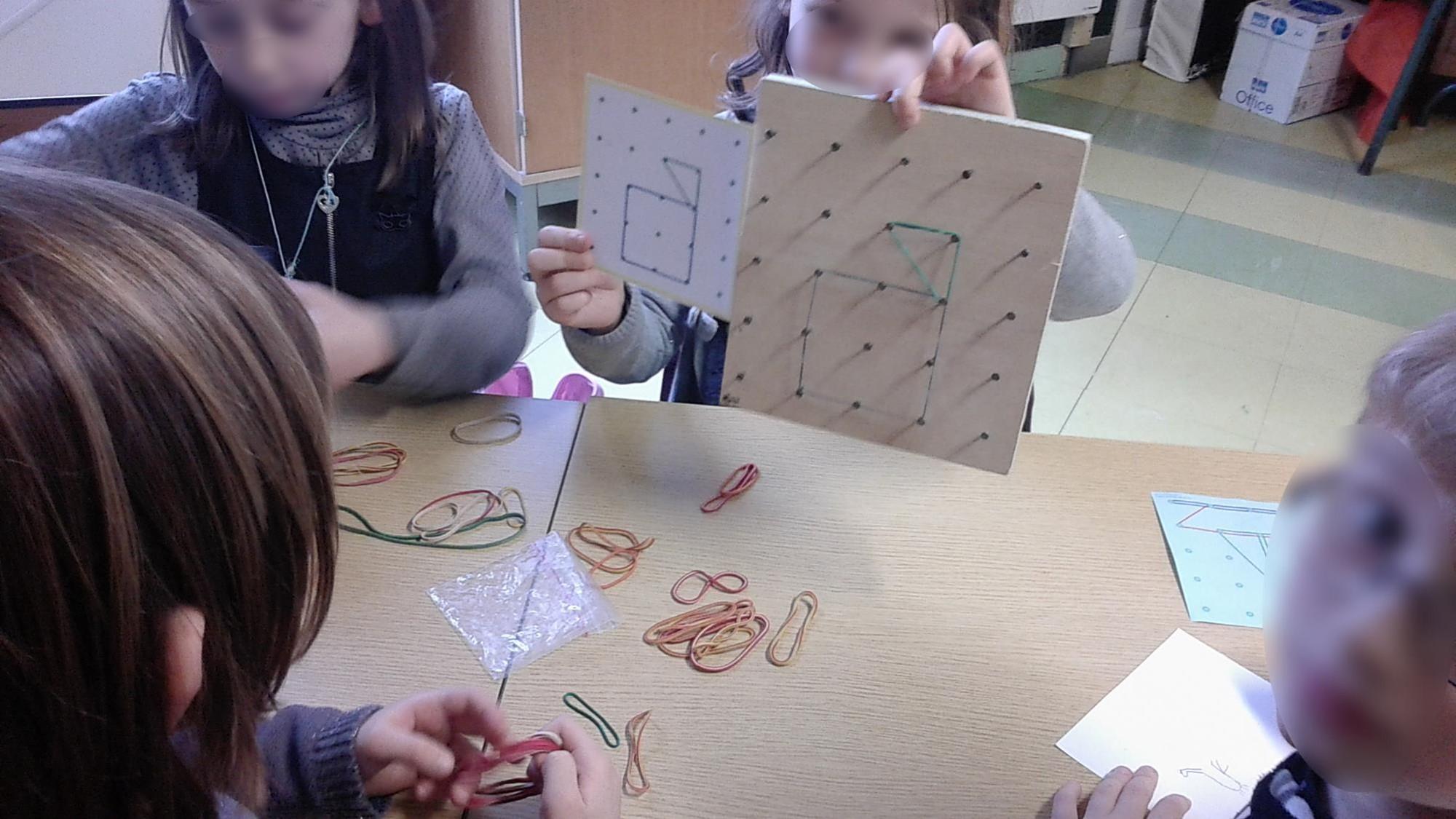 Les élèves comparent les figures sur le dessin et le géoplan