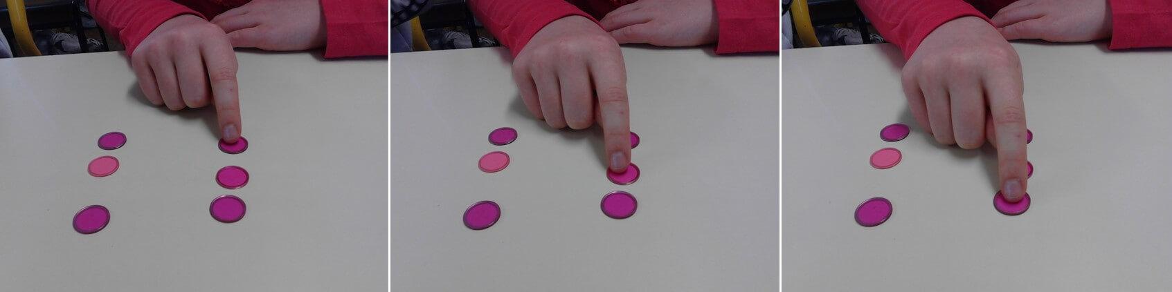 Un élève pointe du doigt les jetons en comptant 1, 2 et 3