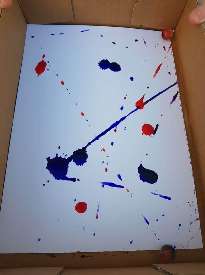 Pendant : chaque enfant fait rouler des billes dans les taches de peinture